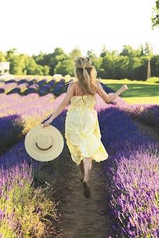 Belle et jeune fille dans un champ plein de fleurs de lavande