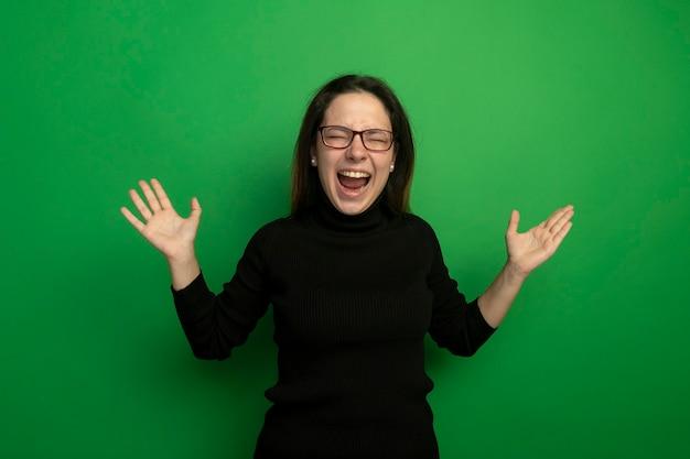 Belle jeune fille dans un col roulé noir et des lunettes criant avec les bras levés heureux et excité