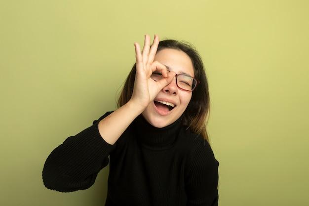Belle jeune fille dans un col roulé noir et lunettes souriant avec visage heureux montrant signe ok