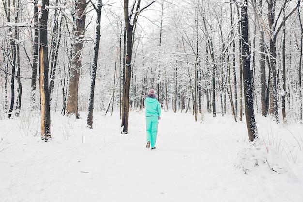 Belle jeune fille dans une forêt blanche d'hiver.