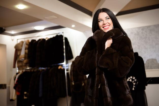 La belle jeune fille dans un manteau de fourrure dans le magasin mesure et choisit des vêtements