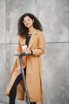Belle jeune fille dans un manteau marron. femme sur un scooter électrique.