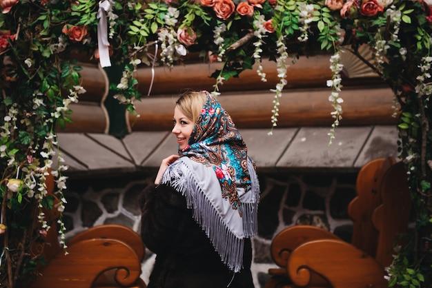 Une belle jeune fille dans un manteau de vison et une écharpe folklorique russe