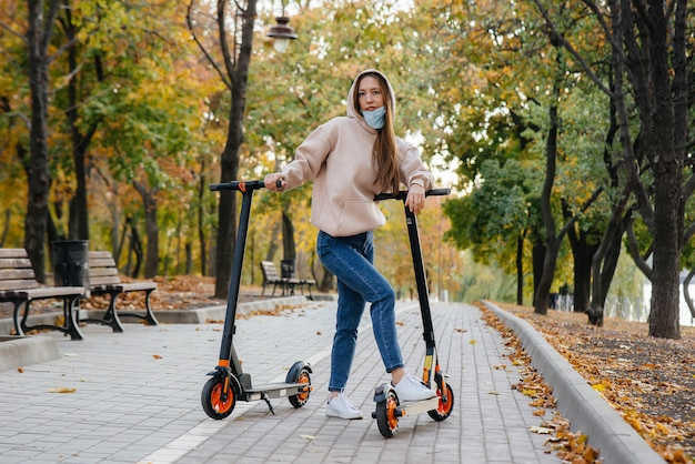 Une belle jeune fille dans un masque monte dans le parc sur un scooter électrique par une chaude journée d'automne. promenade dans le parc.