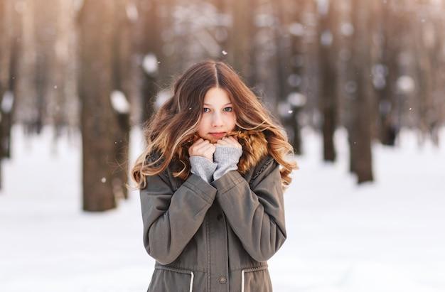 Belle jeune fille dans un parc d'hiver se promène