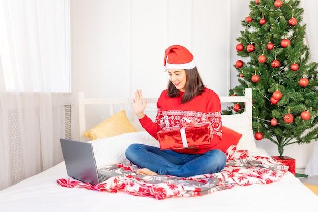 Une belle jeune fille dans un pull rouge et un chapeau fait un appel vidéo avec un cadeau