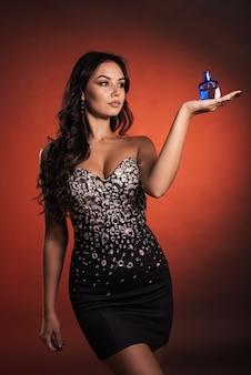 Belle jeune fille dans une robe avec strass posant avec parfum