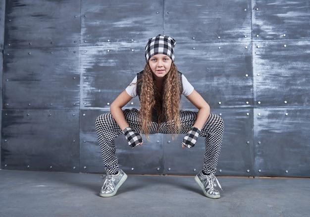 Belle jeune fille dansant dans un vêtement à la mode sur un mur de grunge