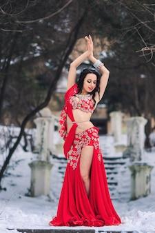 Belle jeune fille dansant la danse du ventre en robe rouge en hiver dans un parc sur la neige.