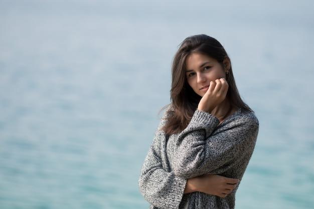 Belle jeune fille debout au bord du lac. portrait de mode de vie dans la nature.