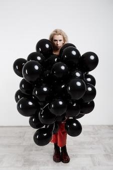 Belle jeune fille debout dans des ballons noirs sur mur blanc.