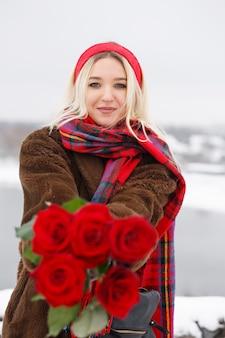 Belle jeune fille donne un bouquet de roses rouges le jour de la saint-valentin