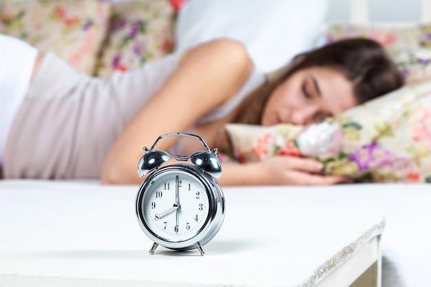 La belle jeune fille dormant dans son lit. le service d'horloge est au premier plan