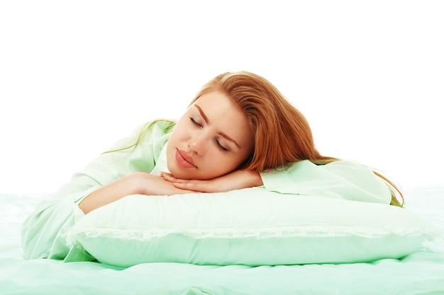 Belle jeune fille dort dans le lit serrant un oreiller sur le ventre
