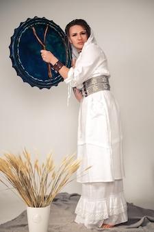 Une belle jeune fille avec des dreadlocks dans un style bohème. avec un tambour ethnique à la main. méditation de repos