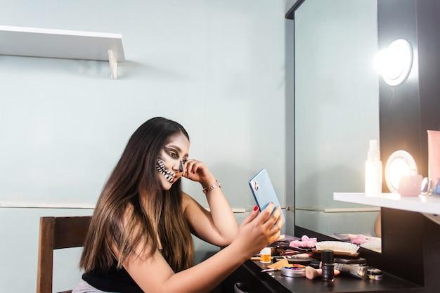 Belle jeune fille avec du maquillage de crâne d'halloween prenant des selfies avec son téléphone intelligent dans sa chambre