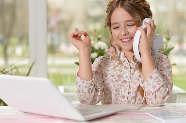Belle jeune fille écoutant de la musique à l'aide d'un ordinateur portable