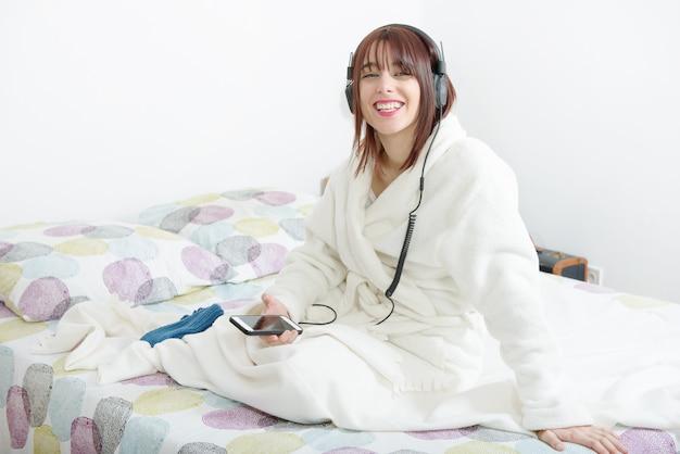 Belle jeune fille écoutant de la musique dans son lit