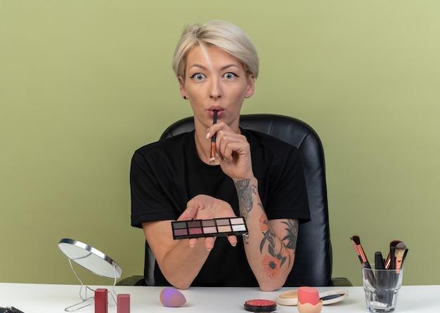 Une belle jeune fille effrayée est assise à table avec des outils de maquillage tenant une palette de fards à paupières avec un pinceau de maquillage isolé sur fond vert olive
