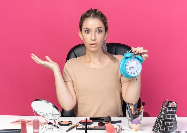 Une belle jeune fille effrayée est assise à table avec des outils de maquillage tenant un réveil isolé sur fond rose