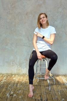 Belle jeune fille effrontée est assis sur une chaise près du mur de briques.