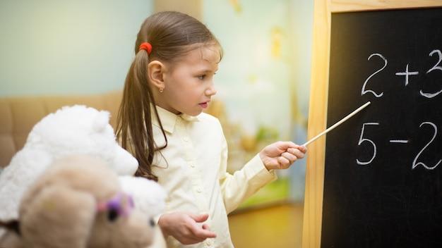 Belle jeune fille enseigne des jouets à la maison sur tableau noir