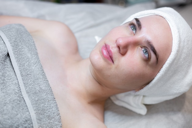 Une belle jeune fille est allongée sur la table de l'esthéticienne et reçoit des procédures, un léger massage du visage à l'huile.