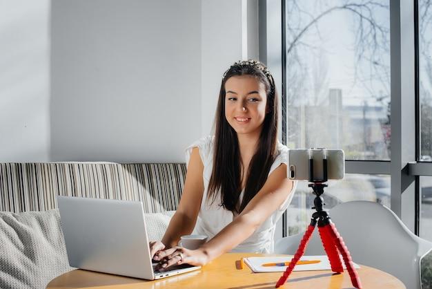 Une belle jeune fille est assise dans un café, enregistre des blogs vidéo et discute sur les réseaux sociaux.
