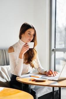 Une belle jeune fille est assise dans un café, travaille devant un ordinateur et communique sur les réseaux sociaux.