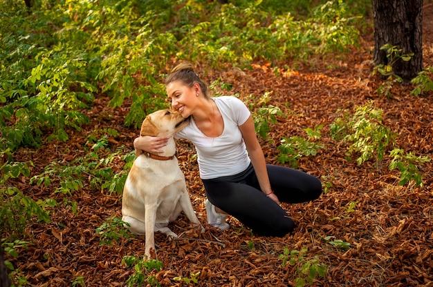 Belle jeune fille est assise dans une forêt avec un chien et embrasse son animal de compagnie bien-aimé
