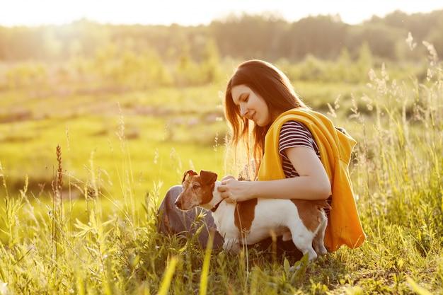 Une belle jeune fille est assise sur l'herbe et étreint son chien