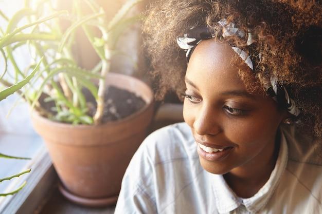 Belle jeune fille étudiante africaine portant un bandana, profitant du temps libre au café après les cours à l'université.