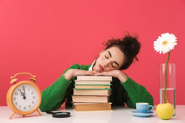 Belle jeune fille étudiante assise à la table isolée, étudiant avec des livres, dormant