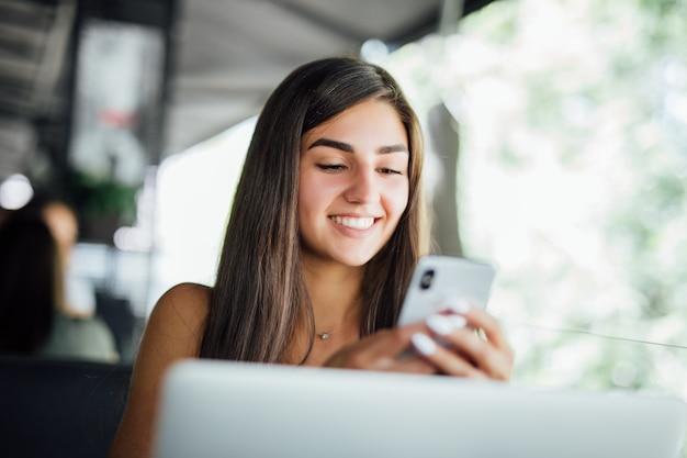 Belle jeune fille étudiante avec ordinateur portable et tasse de thé ou de café au café