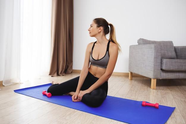 Belle jeune fille faire des exercices de yoga au sol