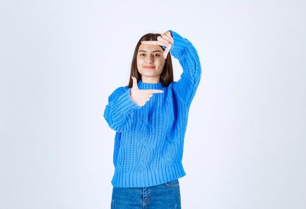 Belle jeune fille faisant le cadre en utilisant les paumes des mains et les doigts.