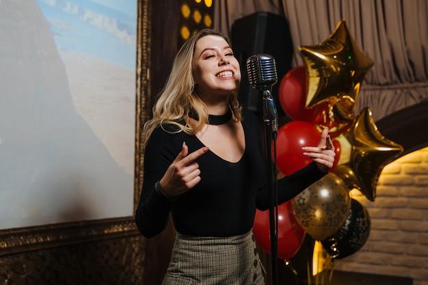 Une belle jeune fille faisant une chanson de karaoké dans une boîte de nuit.