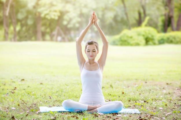 Belle jeune fille faisant du yoga près du lac dans le parc naturel