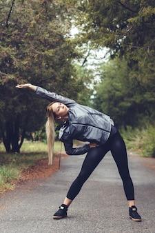 Belle jeune fille faisant des exercices d'étirement dans un parc de la ville à temps pluvieux.