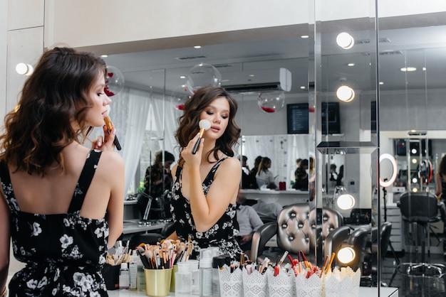 Une belle jeune fille fait un beau maquillage de soirée devant le miroir