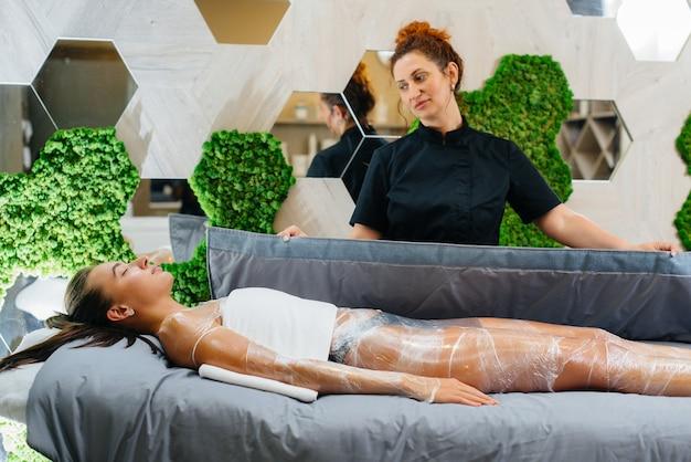 Une belle jeune fille fait une procédure de cosmétologie enveloppement complet du corps dans un salon de beauté moderne. procédures de spa dans un salon de beauté.