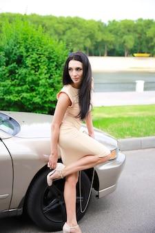 Belle jeune fille sur un fond de voiture et une clé pour tourner les roues