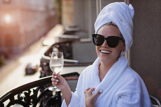 Belle jeune fille heureuse dans un peignoir est assis sur un balcon