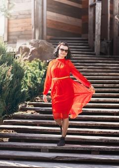Belle jeune fille heureuse descend les escaliers dans une longue robe rouge. charme
