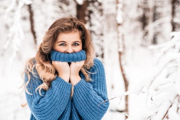Belle jeune fille heureuse en riant portant chapeau d'hiver, écharpe recouverte de flocons de neige. mode de vie actif. fond de paysage de forêt d'hiver.
