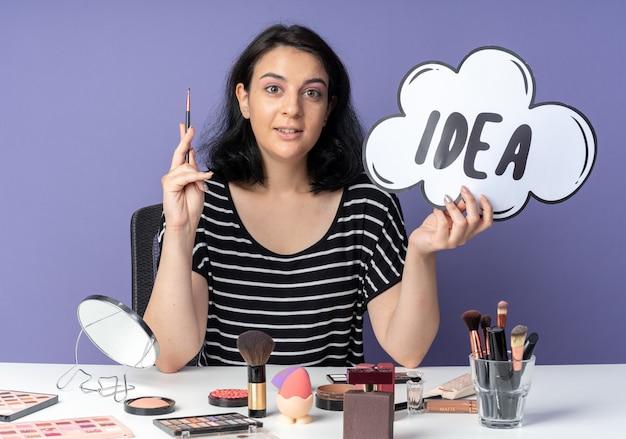 Une belle jeune fille impressionnée est assise à table avec des outils de maquillage tenant une bulle d'idée avec un pinceau de maquillage isolé sur un mur bleu
