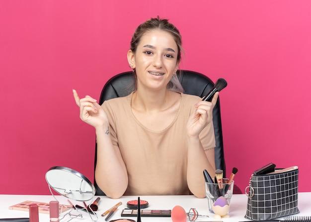 Une belle jeune fille impressionnée portant un appareil dentaire est assise à table avec des outils de maquillage tenant un pinceau à poudre isolé sur un mur rose