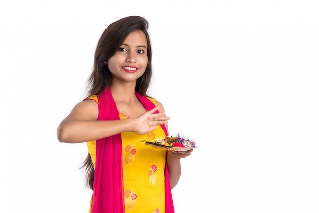 Belle jeune fille indienne tenant pooja thali ou effectuant un culte sur fond blanc