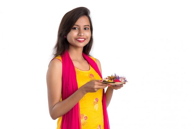 Belle jeune fille indienne tenant pooja thali ou effectuer le culte sur blanc