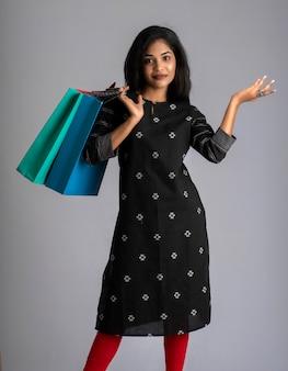 Belle jeune fille indienne tenant et posant avec des sacs à provisions sur fond gris